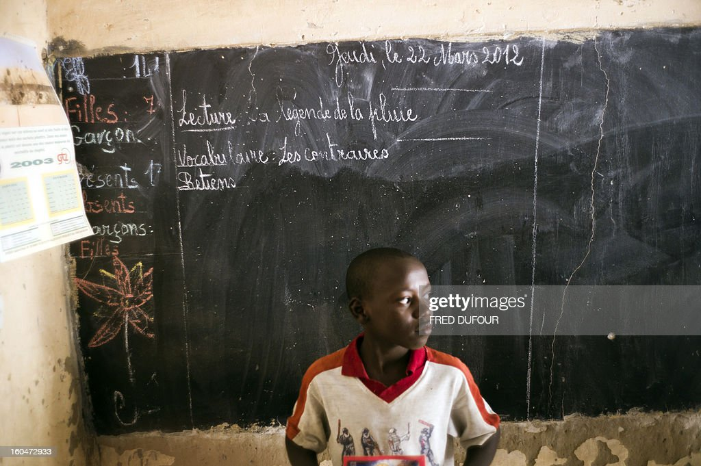 A Malian child stands in front of the black board of his school on February 1, 2013 in Timbuktu, indicating the last day of class on March 22, 2012, as the school re-open today after 10 months of islamists ruling in Northern Mali. French-led troops worked today to secure the last Islamist stronghold in the north after a lightning offensive against the extremists.