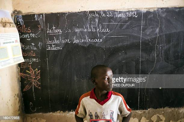 Malian child stands in front of the black board of his school on February 1, 2013 in Timbuktu, indicating the last day of class on March 22 as the...