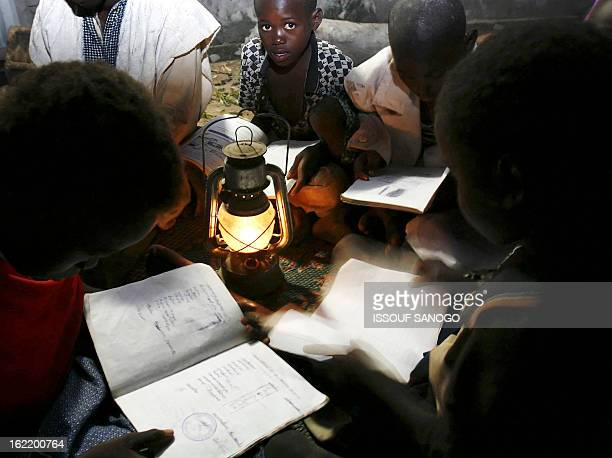 Malian children study 26 July 2006 with an oil lamp in their village Baramba AFP PHOTO ISSOUF SANOGO