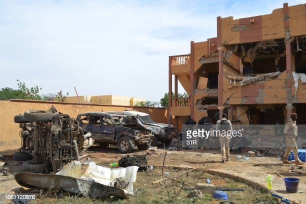 A Malian firefighters and soldiers walks beside a destroyed building and burnt cars on November 13 in Gao after a suicide car bomb attack overnight...