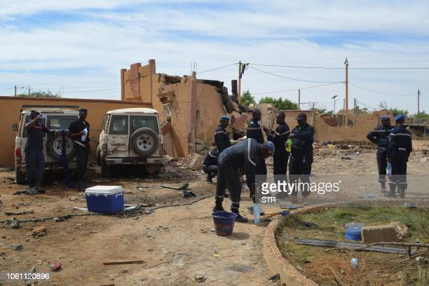 A Malian firefighters stand beside a destroyed building on November 13 in Gao after a suicide car bomb attack overnight which killed three people...