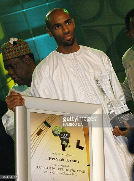 Malian footballer and signing for Sevilla FC Frederic Kanoute holds a certificate and a trophy as Africa's soccer governing body president Issa...