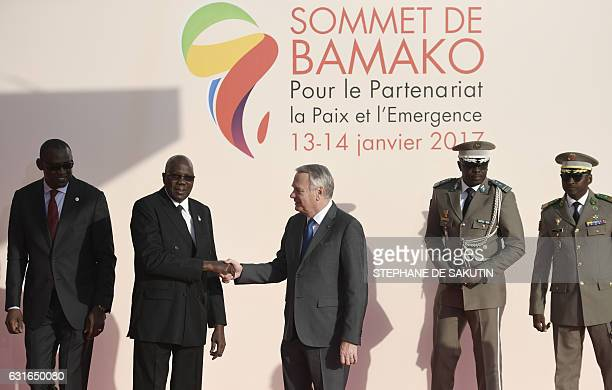 Malian Foreign Affairs Minister Abdoulaye Diop looks over as Malian Prime Minister Modibo Keita greets French Minister of Foreign Affairs JeanMarc...