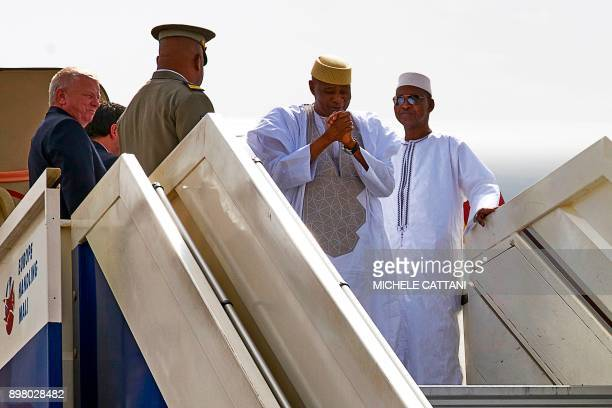 Malian former president Amadou Toumani Toure gestures while disembarking from a plane in Bamako on December 24 as he returns for the first time to...
