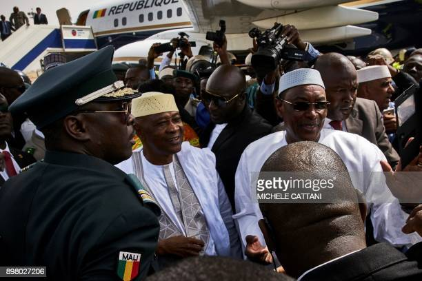 Malian former president Amadou Toumani Toure looks on flanked by Malian Prime Minister Abdoulaye Idrissa Maiga after disembarking from a plane in...
