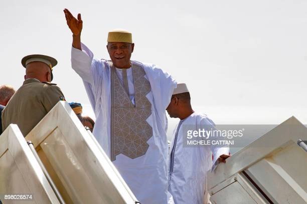 Malian former president Amadou Toumani Toure waves while disembarking from a plane in Bamako on December 24 as he returns for the first time to Mali...