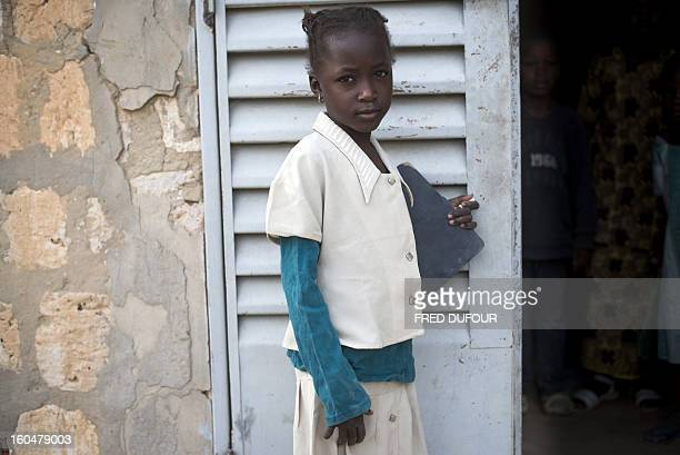 A Malian girl poses prior to attend a class on February 1 in a school of Timbuktu which reopens today after 10 months of islamists ruling in northern...