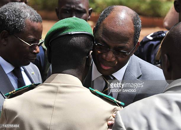 Malian junta leader captain Amadou Sanogo is embraced by Burkina Faso's Foreign Minister Djibrill Bassole after a declaration at the Kati military...