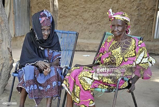 DANIEL Malian Kiniba Konare and Niakoro Coulibaly sit outside the latters home in the village of Kodjan some 60 kilometers west of Bamako on November...
