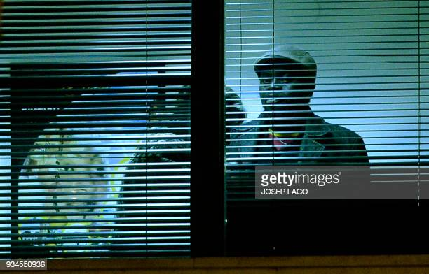 A Malian man looks at the wife of Mali's honorary consul he allegedly has taken hostage inside the consulate of Mali in Barcelona on March 19 2018...