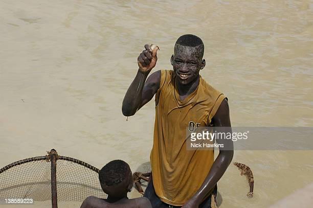 Malian man showing fish he has caught in river Mali