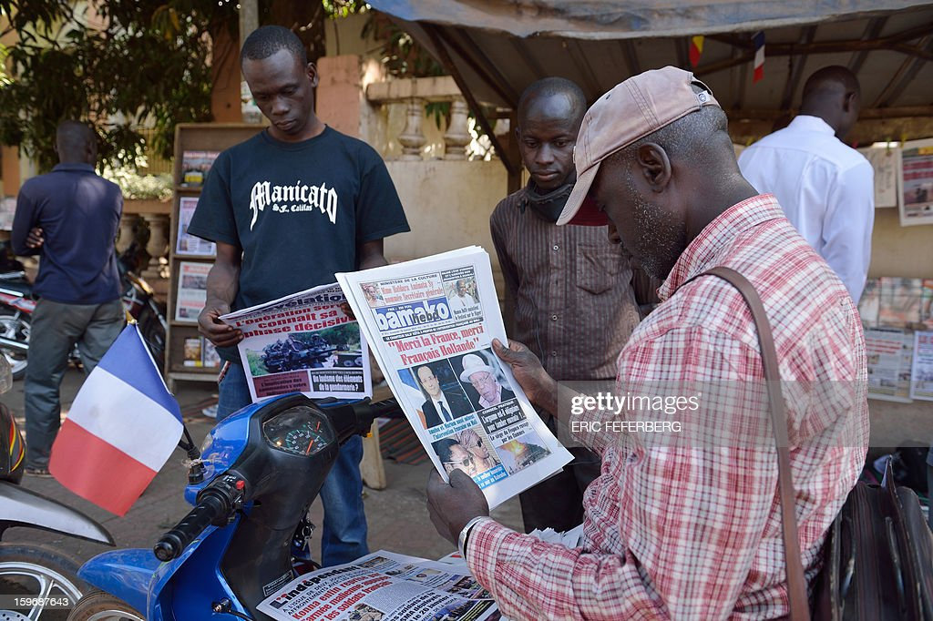 A Malian man sitting on a scooter displaying a French flag reads the newspapers on January 18, 2013 in a street of Bamako. French Foreign Minister Laurent Fabius said he would attend an emergency summit of the west African bloc ECOWAS on Saturday to help accelerate the deployment of an African military force in Mali.