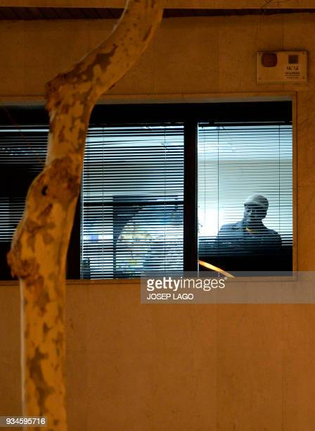 A Malian man who allegedly has taken a woman hostage is pictured through a window of the consulate of Mali in Barcelona on March 19 2018 A man from...
