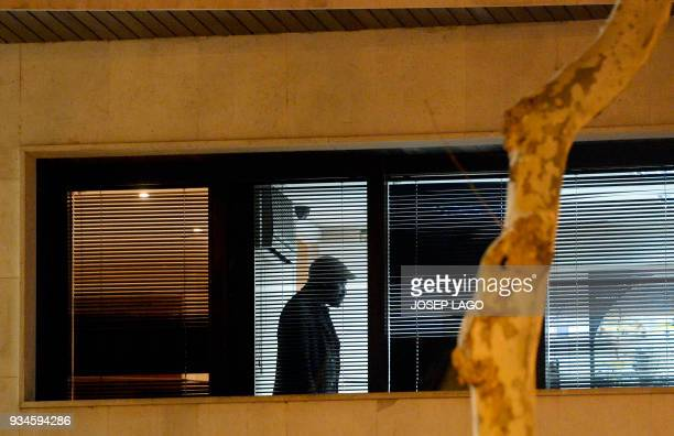 A Malian man who allegedly has taken a woman hostage stands inside the consulate of Mali in Barcelona on March 19 2018 A man from Mali was holding a...