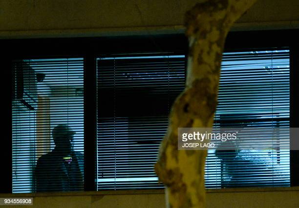 A Malian man who allegedly has taken the wife of Mali's honorary consul hostage is pictured through a window of the consulate of Mali in Barcelona on...