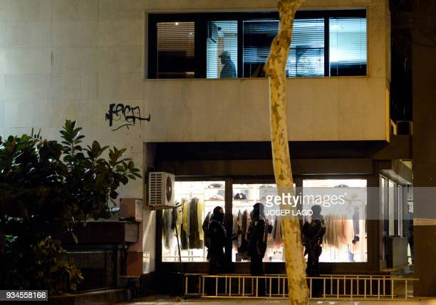 A Malian man who allegedly has taken the wife of Mali's honorary consul hostage stands inside the consulate of Mali in Barcelona as 'Mossos...