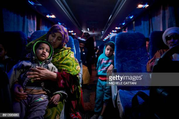 A Malian migrant woman with her children is transferred by bus to a temporary shelter upon their arrival in Bamako on December 13 after being...