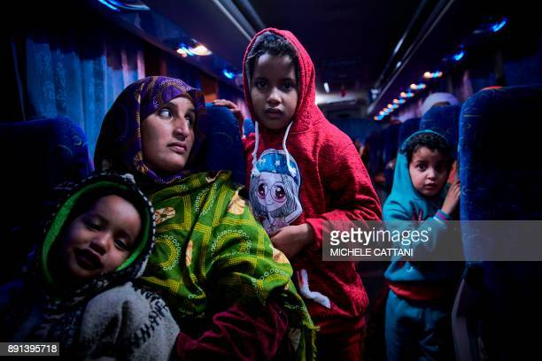 Malian migrant woman with her children is transferred by bus to a temporary shelter upon their arrival in Bamako on December 13 after being...