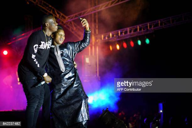 Malian musician Sidiki Diabate poses for a 'selfie' with a young fan as he performs on stage during his concert at Modibo Keita Stadium in Bamako on...