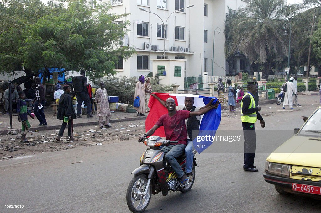 Malian people wave a French national flag on a scooter on January 12, 2013 in Bamako as France sent troops the day before to help Malian forces hold back an advance by Islamist rebels. French President said today that French military intervention had halted the advance of Islamists trying to push south from their northern stronghold.