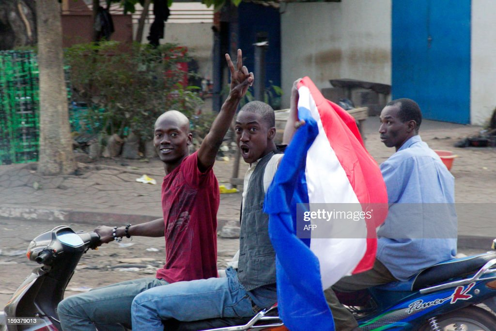 Malian people wave a French national flag on their scooter on January 12, 2013 in Bamako as France sent troops the day before to help Malian forces hold back an advance by Islamist rebels. French President said today that French military intervention had halted the advance of Islamists trying to push south from their northern stronghold.