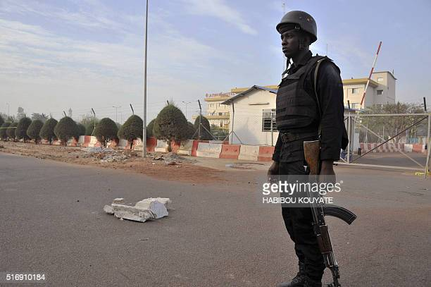 A Malian police officer stands guard in a street near a hotel hosting an EU military training mission a day after an attack in Bamako on March 22...