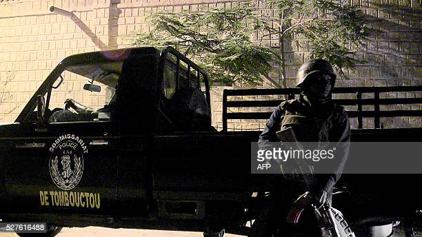 A Malian policeman stands next to a police car on May 2 2016 in Timbuktu during a joint patrol with German and Swedish UN mission in Mali peacekeping...