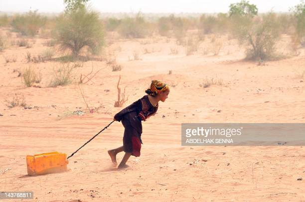 A Malian refugee pulls a jerrican of water at the Mbere refugee camp on May 3 near Bassiknou southern Mauritania 60 km from the border with Mali The...