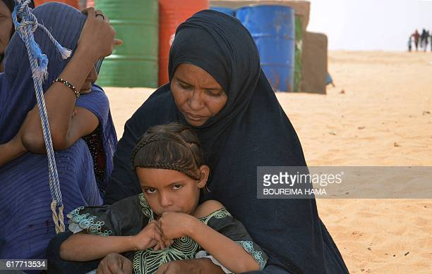 Malian refugees sit in the shade on October 20 2016 at the in Tazalit United Nations refugee camp in the Tahoua region some 300 kilometres northeast...