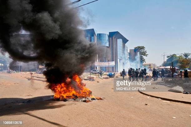 Malian riot police members stand past a fire set by protesters during a protest called by opposition parties in Bamako on December 8 2018