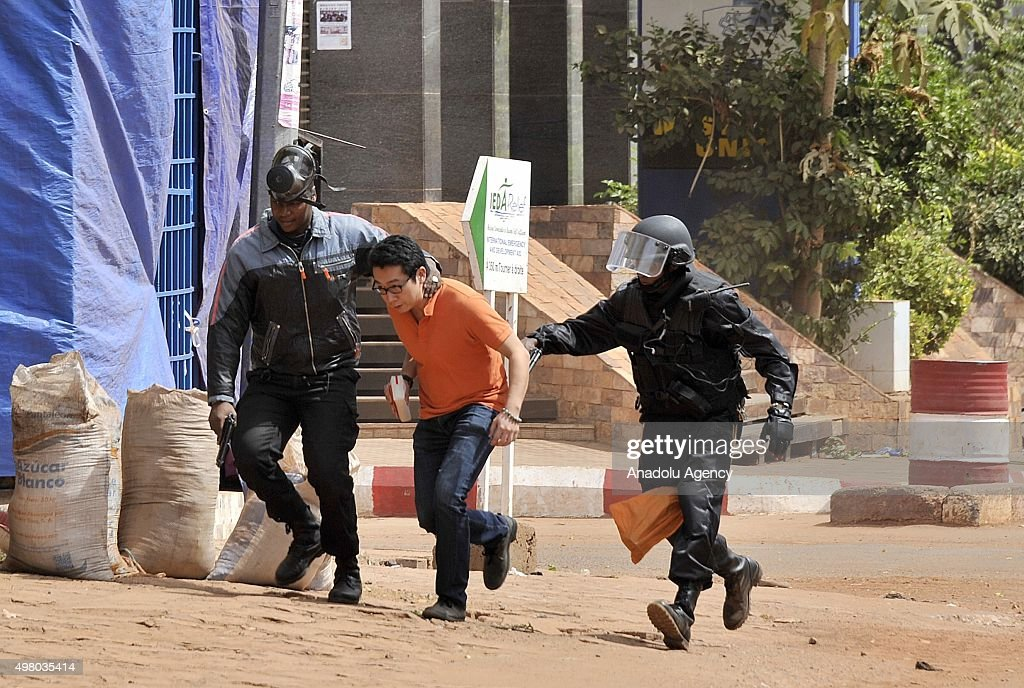 Malian security forces escort a hostage freed from the Radisson Blu hotel in Bamako on November 20, 2015. Gunmen have taken 170 hostages at Radisson Blu Hotel in Mali on November 20, 2015.