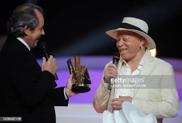 Malian singer Salif Keita receives the award for best world's music album of the year for 'La difference' from Tv host Christian Morin during the...