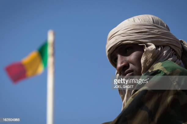 Malian soldier is pictured next to a Malian flag in the centre of Gao on February 24, 2013. Tuareg militias battled Arab rebels in northern Mali...