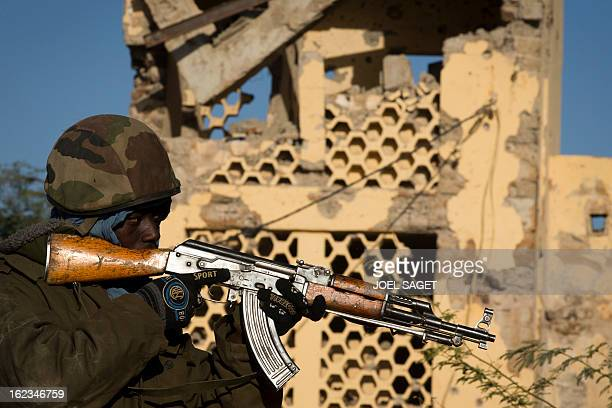 A Malian soldier points his gun in front of the destroyed courthouse on February 22 2013 in central Gao northern Mali Five people including two...