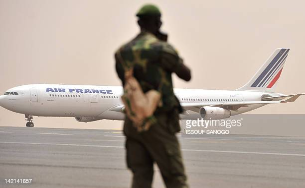 A Malian soldier watches as an Air France aircraft taxis at Bamako airport on March 29 2012 The bloc of West African states set coup leaders in Mali...