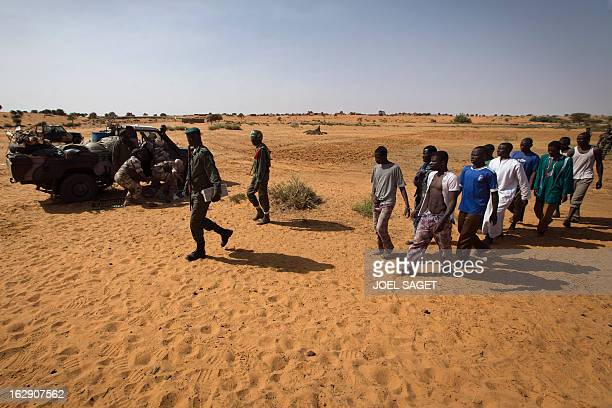 Malian soldiers escort prisoners after they arrived by boat in Kadji on the Niger river on March 1 2013 French and Malian troops launched an...