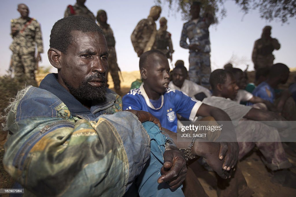Malian soldiers guard handcuffed prisoners after they arrived by boat in Kadji, on the Niger river on March 1, 2013. French and Malian troops launched an operation yesterday in the village of Kadji, northern Mali, where Islamists are hiding out on an island in the Niger river, a military source told AFP.