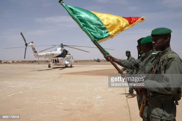 Malian soldiers hold the country's national flag as the helicopter carrying the Malian prime minister lands on May 9 2018 in Menaka Mali The Malian...
