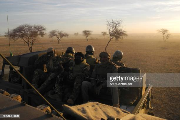 Malian soldiers part of a joint military force the G5 Sahel sit in a vehicle as they patrol on November 2 2017 in central Mali in the border zone...