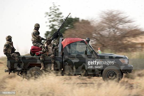 Malian soldiers ride on a pick up truck on February 25 2013 near Gao some 1200 kilometres north of Bamako After recapturing the north's cities from...