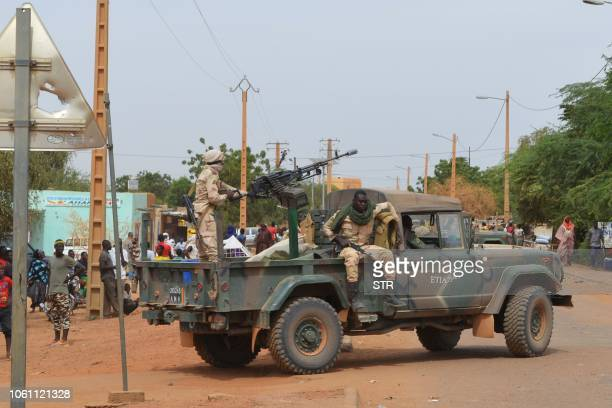 Malian soldiers ride on a pick up truck with a machine gun on November 13 in Gao after a suicide car bomb attack overnight which killed three people...