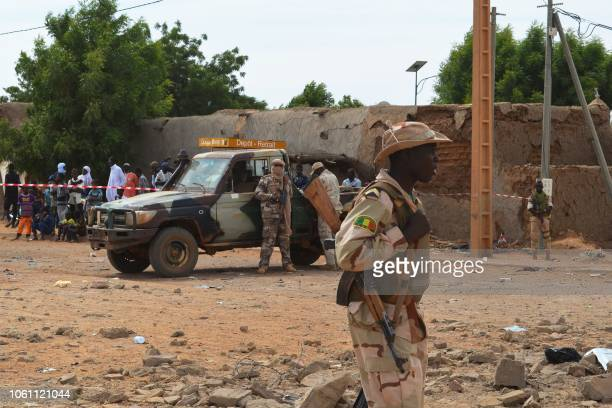 A Malian soldiers stand beside a destroyed building on November 13 in Gao after a suicide car bomb attack overnight which killed three people Three...