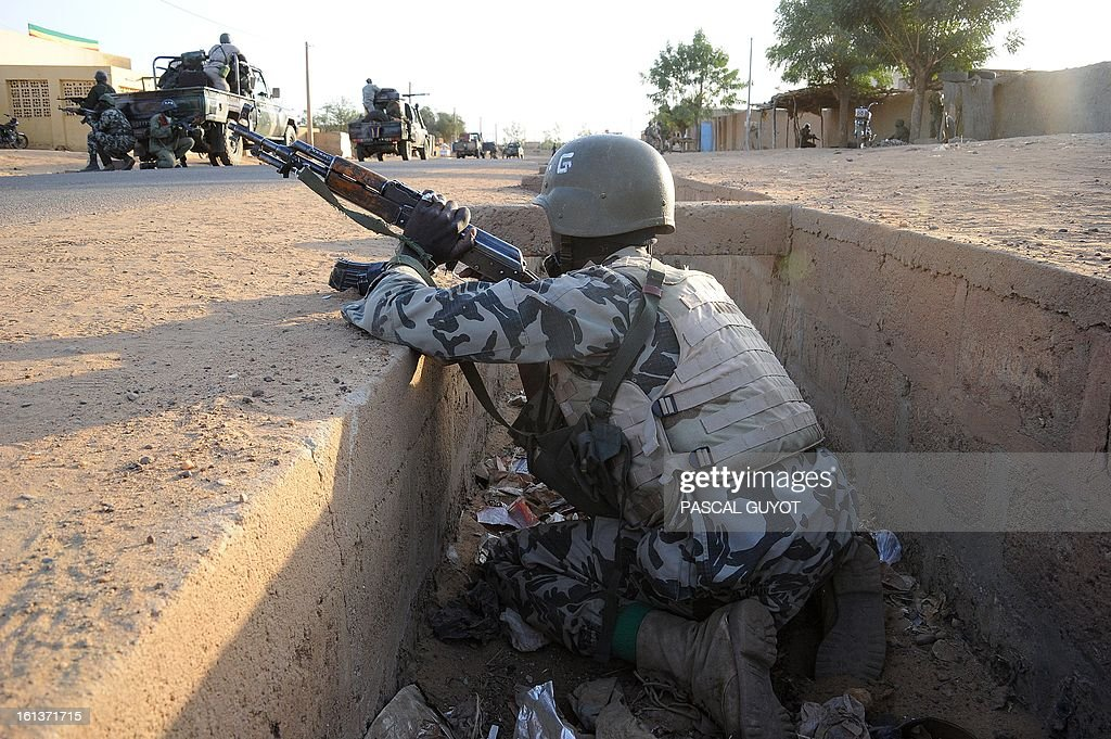Malian soldiers stand guard on February 10, 2013 in the Malian northern city of Gao. Fights between Islamist rebels and Malian soldiers broke out in the center of Gao, recently taken over by the French military to Malian armed Islamist groups, hit by two suicides bombings within two days.