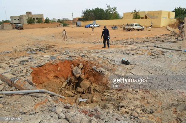 Malian soldiers stand near a hole in the ground caused by the explosion of a suicide car bomb attack overnight which killed three people on November...