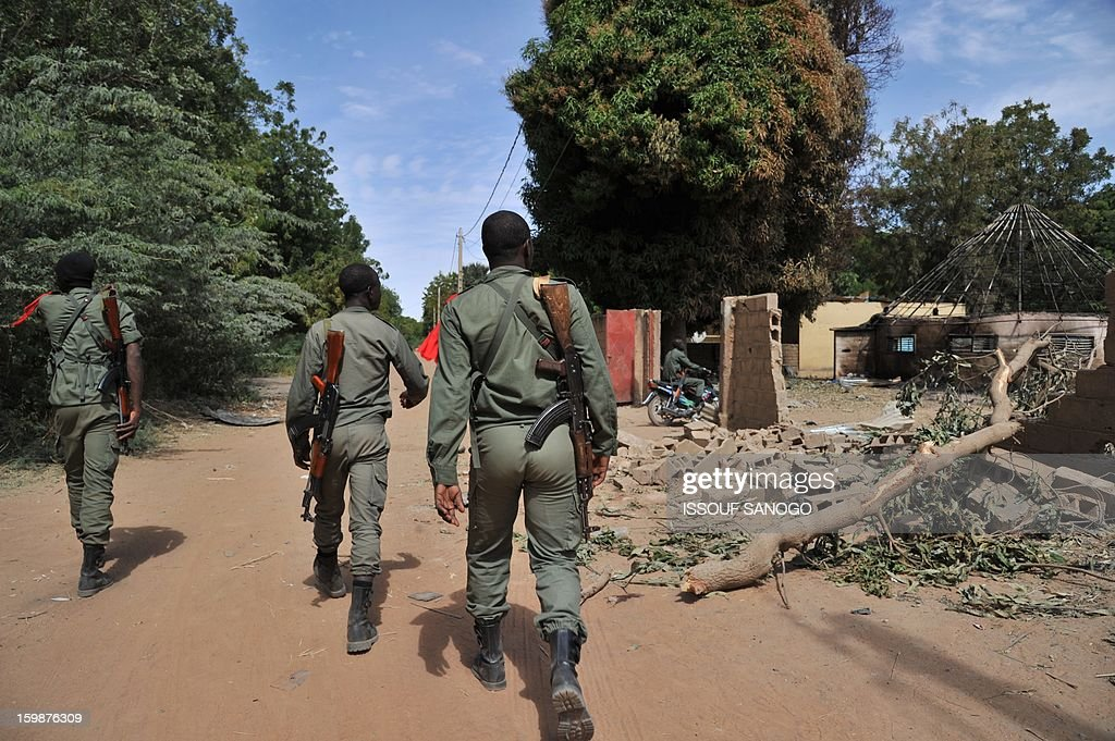 Malian soldiers walk past destroyed army barracks as they patrol in Diabaly on January 22, 2013