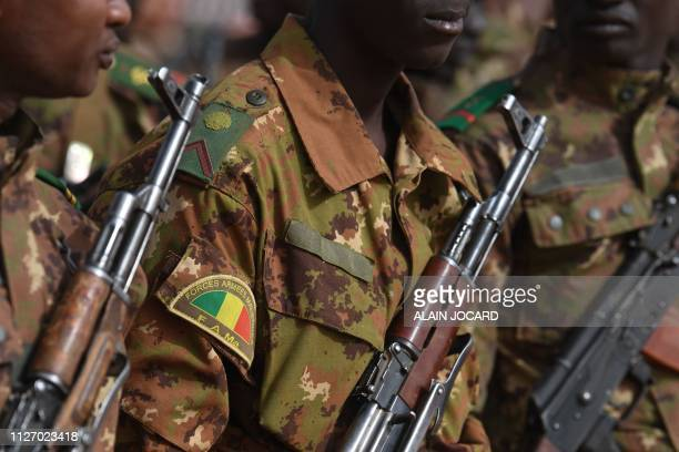 Malian troops stand guard prior to the visit of the French Prime Minister at the Operation Barkane military French base in Gao Mali on February 24...