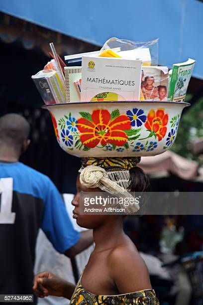A Malian woman walks around the marketplace in Bamako Mali selling school textbooks and journals that she carries on her head in a brightly decorated...