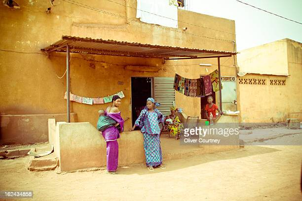 Malian women with their children stand outside a fabric shop in Bamako