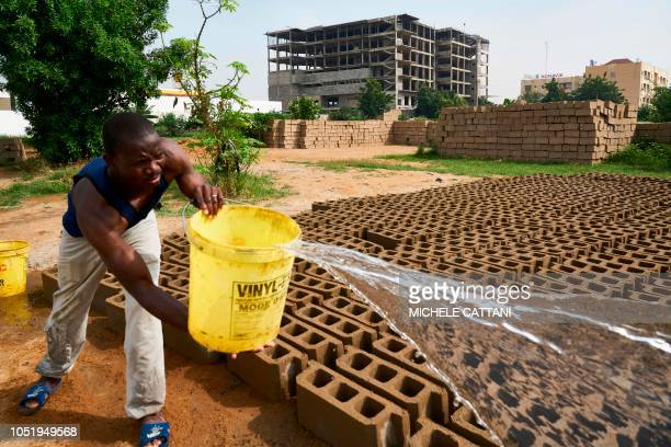 A Malian worker poors water on sun dried bricks made from river sand at a factory in Bamako on October 9 2018 Increasing construction in the Malian...