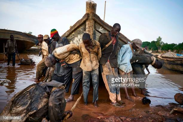 TOPSHOT Malian workers haul out a boat they use to carry sand collected from the river bed during a routine maintenance on October 7 in the port of...